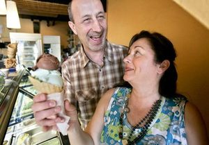 Fainting Goat Gelato owners Yalcin Ataman and his wife, Sevim, hold a cone of mint chocolate chip and Nutella gelato.